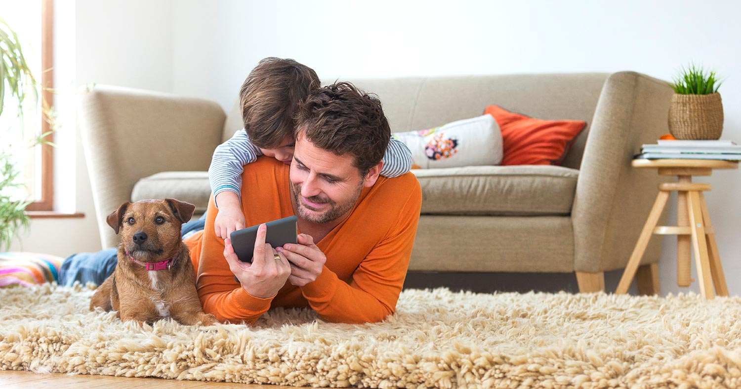 Man boy and dog laying on carpet looking at phone